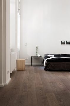 black bedding w/ ashy floor and white walls