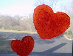 Homemade Valentine Window Cling Craft to do with your kids! All you need is glue, dish soap, and food coloring and you and your kids can make these cute Valentine heart window clings!