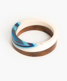 Wood and resin bangle. Crafted from medium coloured real wood and a mix of opaque creamy white and turquoise resin in an interesting layered pattern.
