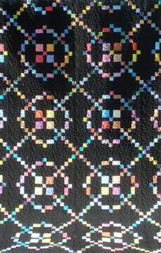 Rainbow Burgoyne Surrounded Quilt on a black background, finished 2010, by sosoquilter55. Close up view.