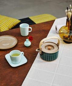 Refresh your decor with a graphic pattern from our early years. In celebration of our founder's visionary spirit, Armi Ratia's Tiiliskivi print adorns this season's homeware. The Oiva (superb) tableware pieces carry a delicate Tiiliskivi relief. The iconic design is also seen in our new, color-blocked home textiles. Brick Patterns, Stoneware Mugs, Marimekko, Lassi, Winter House, Minimalist Interior, Graphic Patterns, Wooden Handles, Colorful Decor