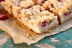 closeup of piece of strawberry rhubarb sugar cookie bars on parchment paper