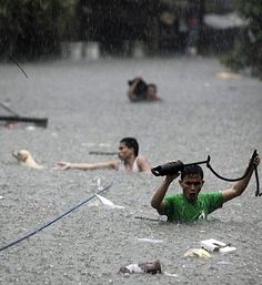 Men cross deep floodwaters in San Juan, north of Manila.