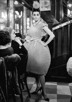 Model in a cocktail dress from Chloé's Spring collection of 1960, at Brasserie Lipp, Paris by unidentified photographer.