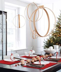 Modern Mobile Chandelier -  Use wooden quilting hoops to create a mobile that floats over a table like a weightless chandelier. Turn the inner ring 180 degrees and wood-glue it to the outer ring at the top. Choose various sizes and hang the spheres at different lengths with clear fishing line and thumbtacks.    From Real Simple.com