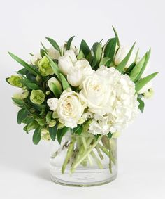 This refreshingly simple design features an elegant collection of crisp white blooms including hydrangea, tulips, roses and our unique heleborus arranged in our signature glass cylinder vase. Tulpen Arrangements, White Flower Arrangements, White Flower Centerpieces, Deco Floral, Arte Floral, White Flowers, Beautiful Flowers, Send Flowers, Exotic Flowers