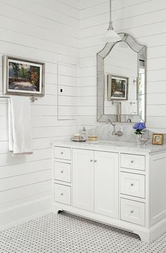 An arched marble backsplash behind the vanity lends a little dimension to this beautiful white bath - Traditional Home®