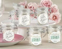 """Our glass favor jars are the perfect antiqued addition to your rustic-themed wedding! Crafted with a hinged top for a hint of delicate vintage flair, these jars come in three looks to express your thanks to loved ones. Depicting treasured trees and fairy-tale flowers in a plumage of cool blues, minty greens and light beige, the too cute designs will make your guests want to show them off. Facts and features: - Glass jar has white-rubber gasket and metal locking device - Jar measures 1.75"""" x…"""