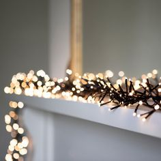 "Warm White LED Cluster Fairy Lights On Black Cable -- ""Dress your home in style with this gorgeous warm white cluster garland, the perfect addition to any winter wonderland. Ideal for candy cane wrapping around large Christmas trees and laying atop fireplaces"""