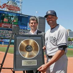 New York Yankees relief pitcher Mariano Rivera holds up a Rock Hall plaque given to him by the Cleveland Indians