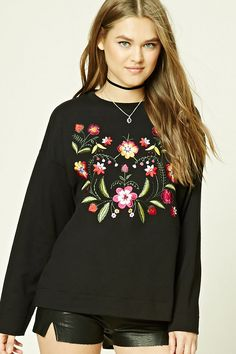 A boxy French terry knit sweatshirt featuring a floral embroidery on the front, ribbed crew neckline, and dropped long sleeves.