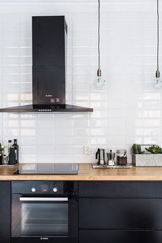 Black kitchen cabinets, white tiles and wood work top in a home in Helsinki, Finland. My Scandinavian home.