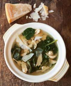 Parmesan Broth with Lemon, Chicken & Spinach  2 small skinless, boneless chicken breast halves (about 3/4 lb./375 g.) 2 Tbs. olive oil 1 small yellow onion, chopped 3 cloves garlic, minced 1-inch (2.5-cm.) piece of Parmesan cheese rind, plus cheese shavings for garnish 6 cups (48 fl. oz./1.5 l.) chicken broth Juice of 1 lemon 1 small bunch spinach, tough stems removed Salt and freshly ground pepper