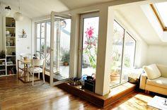 Die Zurückhaltung der Farbgebung verleiht dem Wohn- und Essraum in Komposition mit der lichtdurchfluteten Fensterfront eine helle und freundliche Atmosphäre. Der alte Dielenboden setzt sich charmant in Szene und harmoniert mit dem beigefarbenen Sofa unter der Dachschräge. Schöne Stunden im Freien ermöglicht der große, sonnenverwöhnte Balkon mit vielen Grünpflanzen. Unterstützt wird die Wohlfühl-Atmosphäre durch die weißen Essstühle im Romantik-Look mit geblümter Auflage.