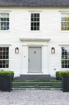 White clapboard, blue stone, sconces