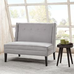 This modern settee with its button tufted detailing and high back provides maximum seating in minimum space. Featured in a silver grey color for a modern update.