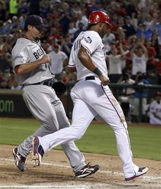 Texas Rangers' Elvis Andrus, right, scores on a wild pitch in front of Boston Red Sox starting pitcher Josh Beckett during the seventh inning of a baseball game on Wednesday, July 25, 2012, in Arlington, Texas. The Rangers won 5-3.  (AP Photo/LM Otero)