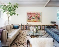 Bohemian Living Room Photo - A glass coffee table surrounded by midcentury furniture and a Moroccan rug