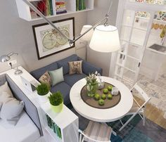 studio moderne aménagé avec un duo chambre salon - lit gris clair, canapé gris foncé, table ronde et meuble de rangement blancs