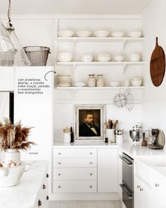 An all-white kitchen, even the dishes that are exposed are white.