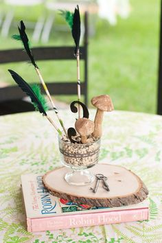 Feathers & Arrows Birthday {Centerpiece with arrows, toadstools, black-eyed peas as filler, arrow ribbon around the glass, keys, wooden slab.}