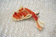 This koi kanzashi has been reserved for Kim Geiger only.  In Japan, the koi (carp) is a symbol of good fortune. Koi streamers are flown during the Boys Day festival to represent parents hope that their sons will show courage and strength. This koi clip is composed of 58 squares of silk. Every piece is hand-dyed in subtle tones. The length is approximately 2 inches long. This piece has been mounted on an alligator clip for easy wear.