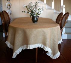 This may be a little too rustic. Burlap tablecloth with linen ruffle. You could use any color burlap.