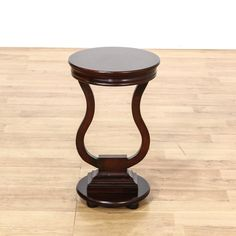 This end table is featured in a solid wood with a dark stain. This traditional style side table has a round top, lyre-shaped pedestal, and round base. Elegant table that's perfect for displaying decor! #americantraditional #tables #endtable #sandiegovintage #vintagefurniture
