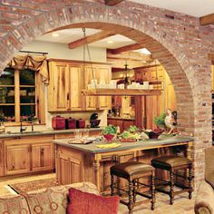 Love the brick archway - Salvage Kitchen     The builder used aged cypress, salvaged from an old mill, to construct the kitchen cabinets and for facing some of the appliances, such as the icemaker and refrigerator. The reclaimed wood was cut, planed, and then made into cabinetry. A light finish lets the natural grain remain visible.