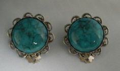 Turquoise Stone Antique Silver Clip On Earrings. Circular simulated turquoise center stone. Stone has black accent lines in it. Silver tone antique looking surround. Silver tone backing and clip.