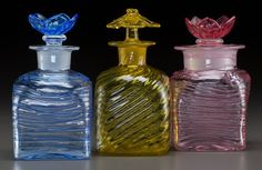 3 threaded and swirled coloured glass perfume bottles with floriform stoppers by Steuben , USA c. 1925