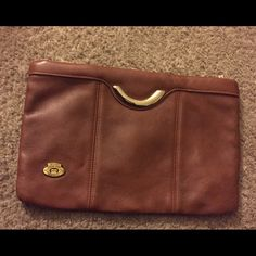 Aigner Authentic Clutch True tan color  leather. Hard to capture color - main photo is closest. Uncommon Aigner!  Burnished golden sturdy metal zipper with Aigner marked zipper pull and hardware perfect. Aigner logo in front antiqued with age.  Leather is thick, supple and buttery soft. Beautifully rolled leather around zipper. Thread is perfect. No cracks, odor or holes. Aigner Bags Clutches & Wristlets