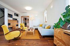 Žlté retro kreslá Halabala a drevená podlaha určili farebnosť a štýl celého interiéru. Stena, ktorú podľa návrhu dizajnérky vyrobili stolárski majstri, oddeľuje schodisko a zároveň ho presvetľuje.
