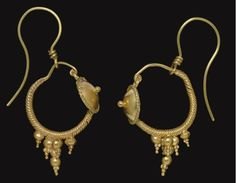 Roman gold earrings, 2nd century A.D.  With a hoop of spiral twisted wire tapering to a plain wire at each end, a shield joined to the hoop, a protruding knob at the center, enclosed within a border of twisted wire, a fixed pendant below of seven hollow spheres, ornamented with inverted granulated pyramids, modern gold earwires joined to the hoop, 2.9 cm. Private collection
