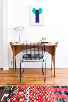 """Inside Jewelry Designer Kathryn Bentley's Home: """"I started painting this a little over a year ago. I've always painted—I find it to be really meditative. There is no real expectation for the paintings, I'm not trying to sell them. [It's] more just a process of opening up and getting some ideas flowing."""" Over  wooden desk with wire frame chair. 
