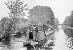 A canal boat loaded with fruit pulp travels along Regent's Canal, on its way from Regent's Canal Dock to the Grand Union Canal, and on towards the Midlands. The boat (registered at Rickmansworth) is being steered by a boatman and his son, in 1944.