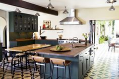 Kitchen with black and white tile floors, white walls, wooden barstools, wooden table, and silver light fixtures