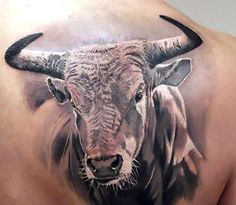 A tattoo consiting of a 3D head of a bull with sharp horns on the back of the wearer. Style: Black and Gray. Tags: Nice