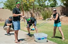 Three team members use the water balloon launch to launch sponges filled with…