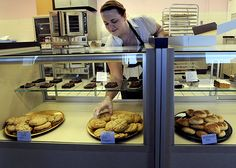 Alison Kanealy, owner of Ali Cakes, places cookies in the display case at her store at 300 Main St. The bakery held its grand opening on Thursday. Photo by Nirmalendu Majumdar/Ames Tribune  http://amestrib.com/news/sweet-treats-main-street