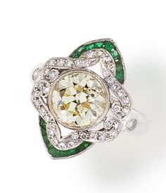 A diamond and emerald ring  centering an old European-cut light yellow diamond within a scrolling surround of round brilliant-cut diamonds and further accentuated by calibré-cut emeralds