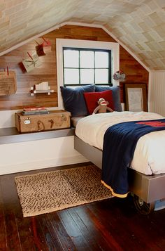 Boys attic bedroom | book pages on the ceiling, rolling platform bed, & wood accent wall | Kara Paslay Designs