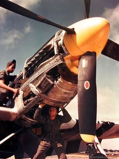 Crew Chief inspects the oil lines on a North American F-51 at an 8th Air Force base somewhere in England. The Assistant Maintenance Chief is underneath checking the hydraulic pump.