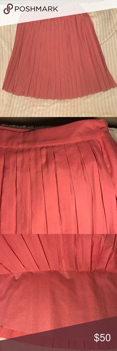 """Talbots coral pleated skirt This skirt is a beautiful coral color! It is made of two layers. The inside layer is 100% cotton and the top pleated layer is 52% cotton and 48% polyester. It is lightweight and would be perfect for spring or summer. It has a couple of very small markings on the waistband (last photo) where the security sensor was located. It has an eye and hook closure with a zipper on the left side. It is 25"""" in length from waistband to the bottom hem. Talbots Skirts"""