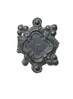 Part of a pilgrim badge, probably of the Rood of Grace, Boxley Abbey. This fragment depicts the terminal of one of the limbs of a crucifix. The terminal is decorated with a barbed quatrefoil, with a trefoil crocket at each barb. In the centre of the quatrefoil is a faint star or sunburst motif. Late Medieval; 14th-15th century ID no: 81.65/33