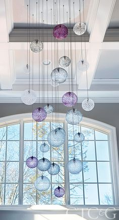 This multi-colored hand-blown chandelier adds sparkle and glamour in this foyer. Via Cottages & Gardens.