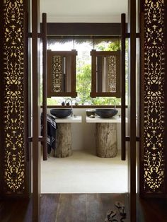 Wonderful use of carved wooden screens: made of earthy materials, but carved in traditional Oriental patterns which permit delicate patterns of light to break through.  Romantic, discretely, seductive.  Must include these elements in the bathroom remodel.  Were the screens to open laterally (barn-door hardware) they would not obstruct wheelchair access.