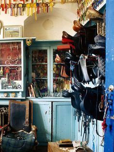 Beautiful tack room with distressed wood cabinetry used to store equipment