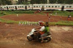 Memanfaatkan Ruang Terbuka  Anak-anak bermain sepak bola di atas gundukan tanah yang sudah diratakan untuk pembangunan rel dwi ganda kereta api lintasan Manggarai-Cikarang di Kelurahan Jatinegara, Kecamatan Cakung, Jakarta Timur, Selasa (31/1/2012). Minimnya ruang terbuka hijau dan ruang publik di DKI Jakarta membuat lahan kosong menjadi incaran anak-anak untuk bermain.