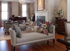 A plush daybed separates the sitting room and piano area from the dining room. Although distinct spaces, Gillies unified thetwo areas with a common color palette. The floral patterned throw pillow on the daybed matches the flower centerpiece and artwork in the dining room.